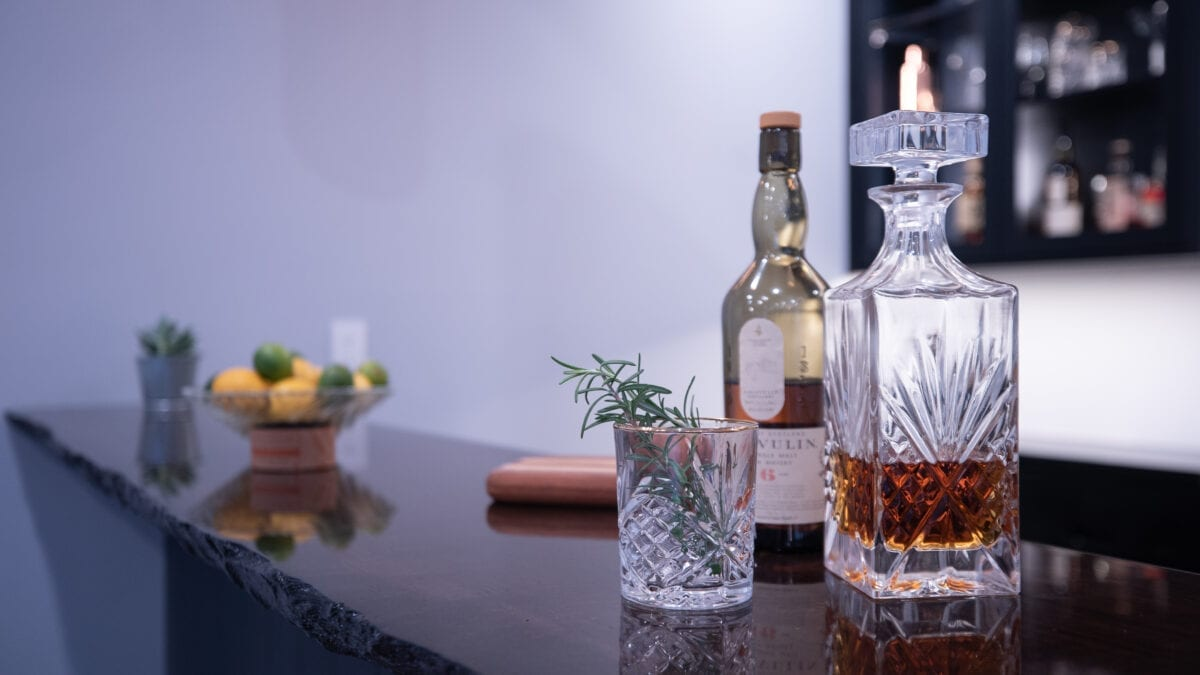 Photo: Wooden bar top with raw edges, decanter, greenery, and citrus