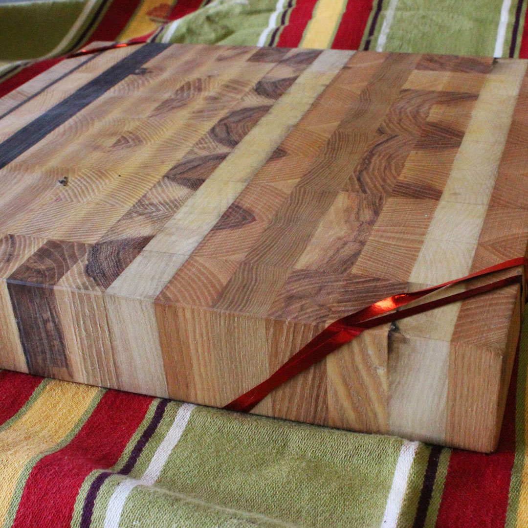 Photo: Thick wooden cutting board made from different cuts of wood on a multi-colored background