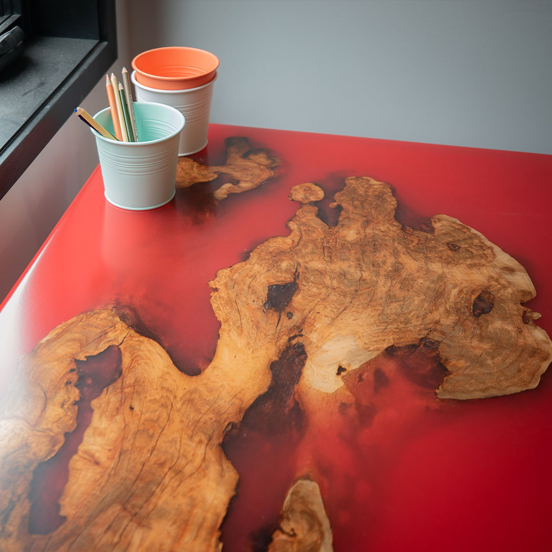 Photo: Custom-made red epoxy table with a cup of colored pencils
