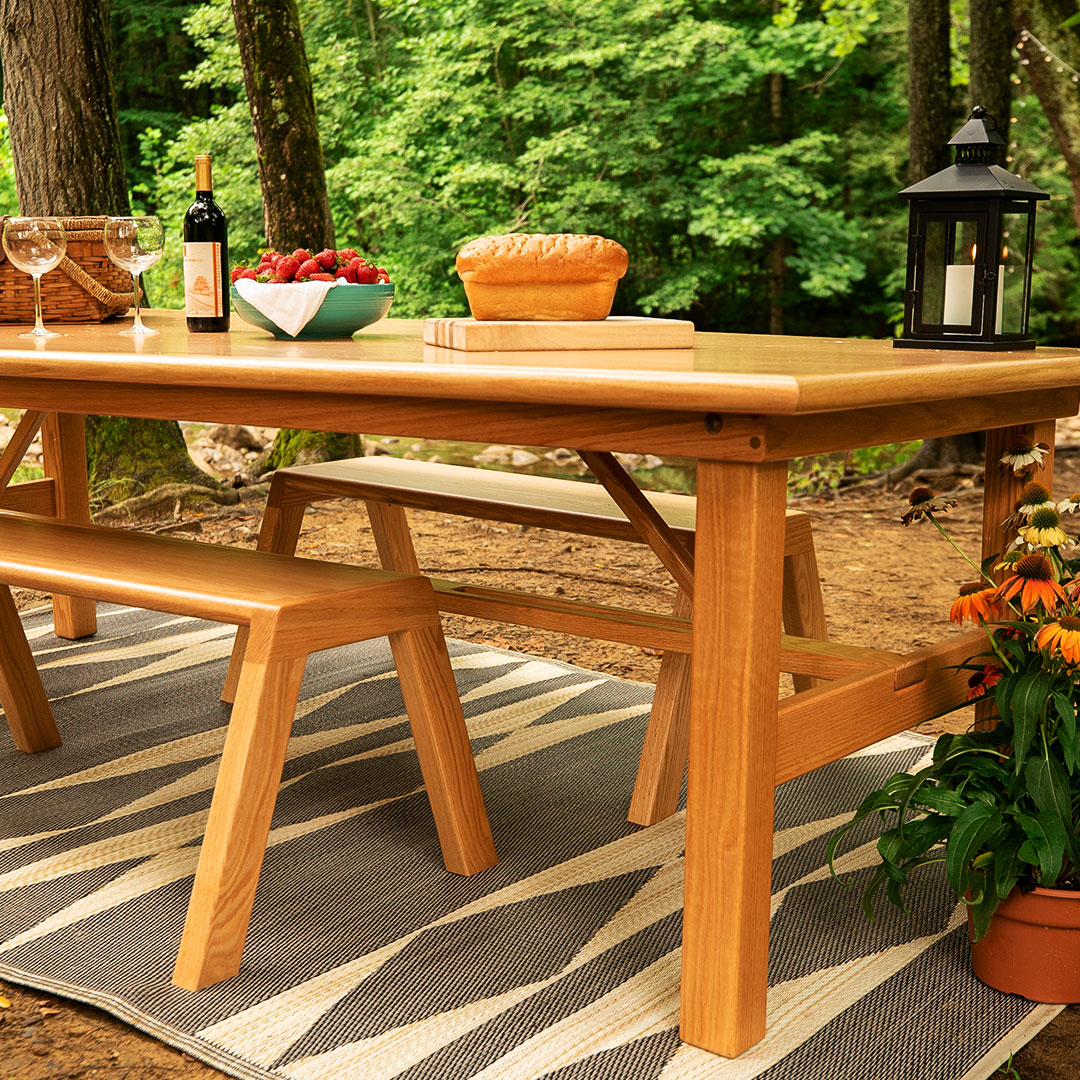Photo: Folding Farmhouse Table and benches styled with a picnic in the woods in summer.